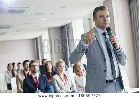 Businessman pointing while speaking through microphone during seminar in convention center