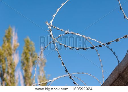Safety fence of barbed wire against the blue sky