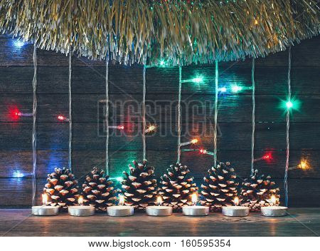Festive new year and Christmas concept. Colorful lights of garlands fir cones and candles on the background of old barn boards. Tinted photo