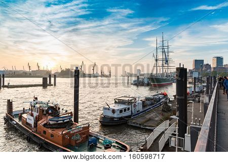 Hamburg, Germany - November 01, 2015: Panorama view on famous ships along the river Elbe quai in the harbor of Hamburg - red tug boat Kristin and sailing ship Rickmer Rickmers.