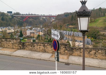 View on the part of old town of Luxembourg City with a road sign to the Casemates and a retro street lamp in the front and the red Grand Duchess Charlotte Bridge and the Kirchberg in the background