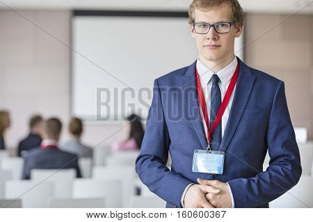 Portrait of confident businessman standing at seminar hall with colleagues sitting in background