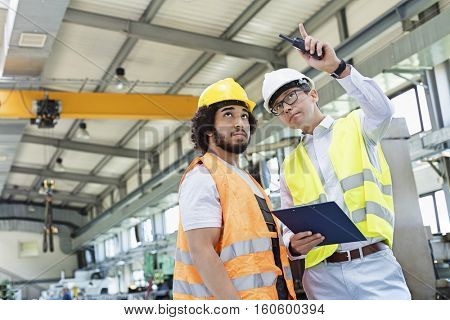 Supervisor showing something to manual worker in metal industry