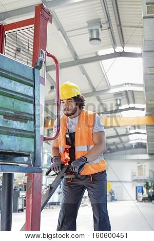 Young male worker pushing hand truck in metal industry