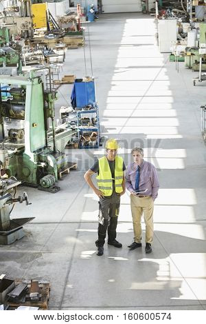 High angle view of supervisor and manual worker having discussion in metal industry