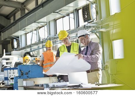 Architect and manual worker reading blueprint at table in industry