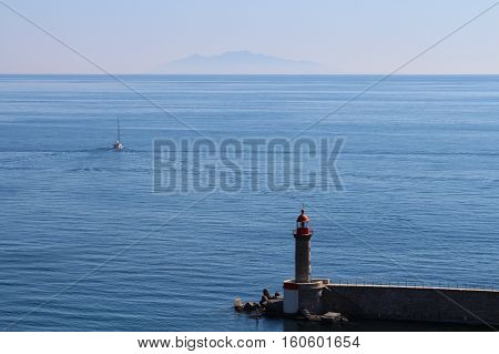 The view of lighthouse and boat heading to a ghost island.