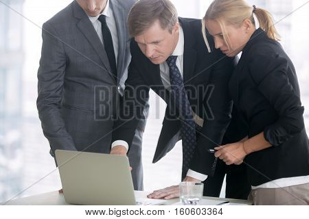 Group of three business partners discussing new project at meeting in office room, using laptop. Middle aged businessman explaining idea showing presentation on laptop screen. Business vision concept