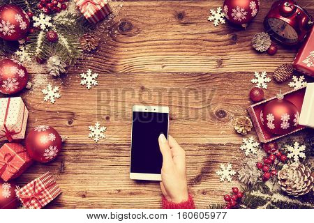 Woman using a touch screen smart phone, hands close up, top view, desktop with gifts and Christmas letters on background