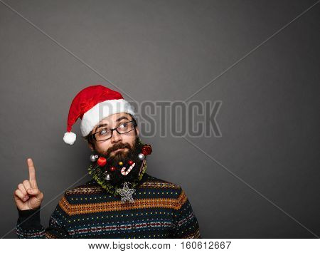 handsome man with decorated christmas beard in red santa claus hat gesturing upwards with his finger to copy space above his head over grey background