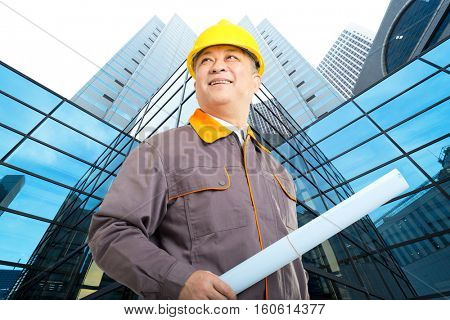old asian man engineer with blueprint and modern office construction