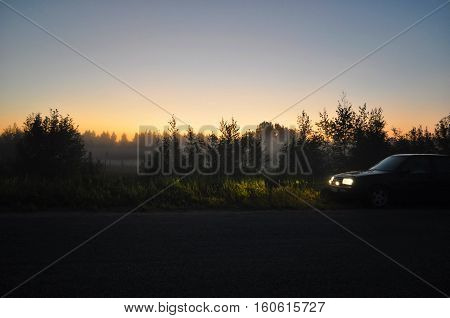 A car standing near the road at night. Bright headlight.