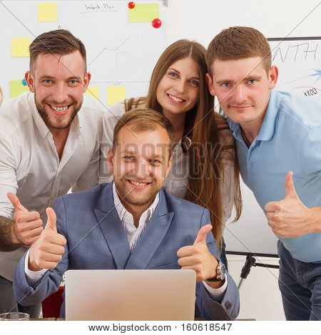 Happy smiling business people group portrait near laptop in the office. Successful team of female and male coworkers show thumbs up, partners and colleagues.