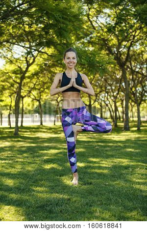 Beautiful happy caucasian girl doing yoga holding a tree pose vrikshasana in the sunny park summer day. Lifestyle healthcare connecting with nature harmony.