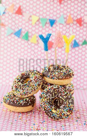 Stack of donuts with chocolate frosting and colorful sprinkles