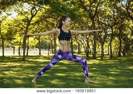 Beautiful girl doing yoga in the park holding a warrior pose or virabhadrasana 2. Healthy lifestyle harmony relax.