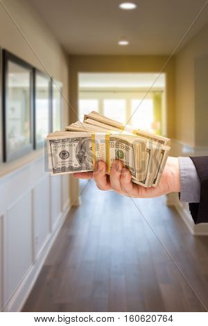 Male Hand With Stack of Cash Inside Hallway of New House.