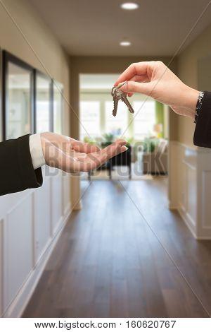 Woman Handing Over The Keys Inside Hallway of New House.