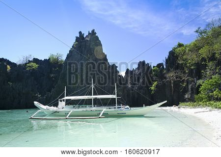 El Nido PhilippinesS - May 18 2007: banka outrigger tour boat in hidden lagoon where tourists swim . El Nido is one of the top tourist destinations in the world.