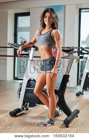 Muscular young woman working out on the exercise bike at the gym, intense cardio workout. She is smiling and looking at the camera