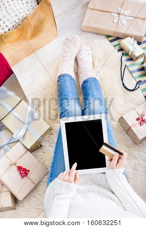 Christmas online shopping above view. Female buyer makes order at screen of tablet. Woman buys presents prepare to xmas eve, sits among gifts boxes and packages. Winter holidays sales