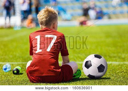 Young Soccer Football Player. Little Boy Sitting on Soccer Pitch. Youth Football Player in Red Soccer Jersey