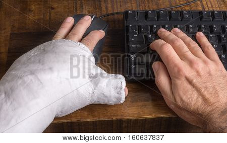 Young Man With Arm Cast Using A Computer Mouse