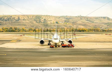 Front view of modern airplane at terminal gate ready for takeoff - International airport with soft desaturated color tones - Emotional wanderlust concept and travel around world on nostalgic filter
