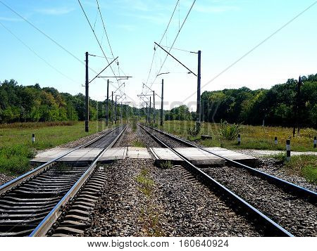 Double-track railway line crosses a highway through the crossing.