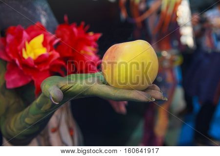 Forbidden fruit in the hand of the devil. Allegory