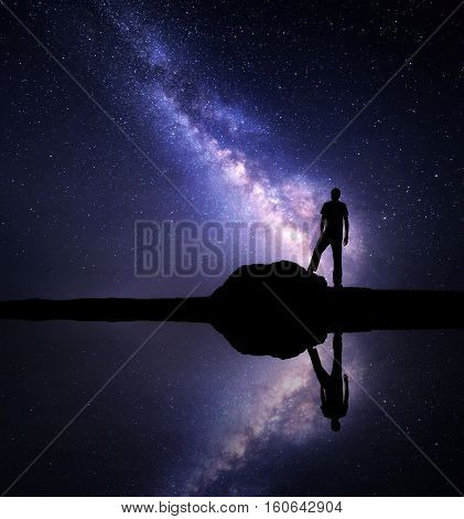 Milky Way. Night starry sky and silhouette of a standing alone man on the stone near the river with sky reflection in water. Milky way and man on the mountain. Galaxy and silhouette of a man. Universe