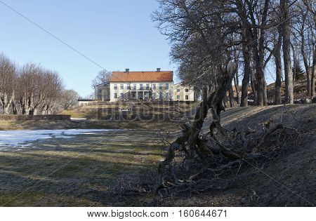 UPLAND, SWEDEN ON APRIL 11. View of a garden, park, fallen branch and a main building in the background on April 11, 2013 in Upland, Sweden. Sunny and chilly morning. Editorial use.