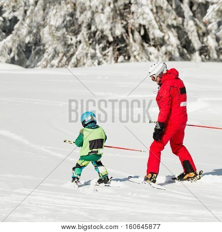 Little boy learning how to ski. Father and son skiing together