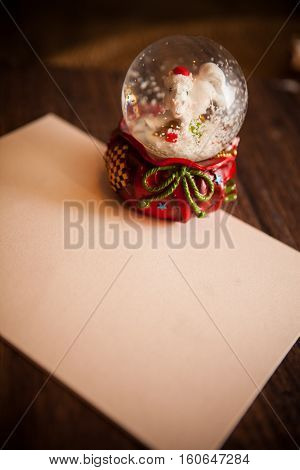 snow globe and white paper on wooden table