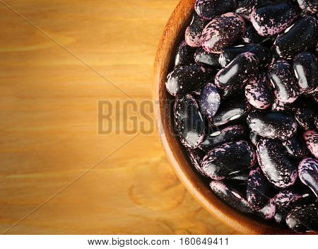 Bowl with black haricot beans on wooden table