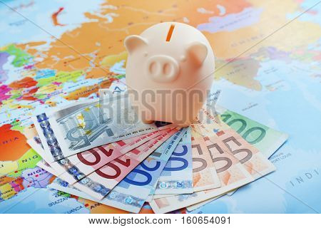 Pig moneybox and Euro banknotes on world map background