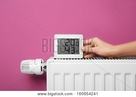 Female hand holding electronic thermometer near heating battery