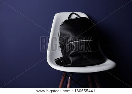 Black leather rucksack on white chair and dark background