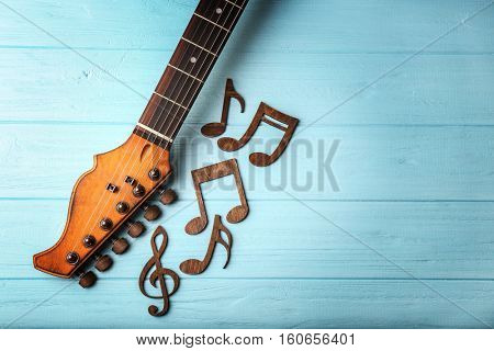 Guitar neck and music notes on color wooden background