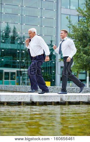 Two business people running fast to an urgent meeting