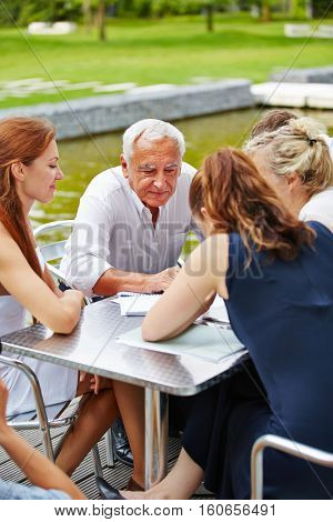 Senior manager sitting with his business team in a meeting outdoors at a table