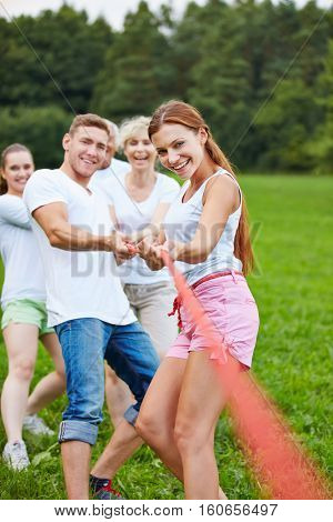 People playing tug of war with rope during a competition outdoors