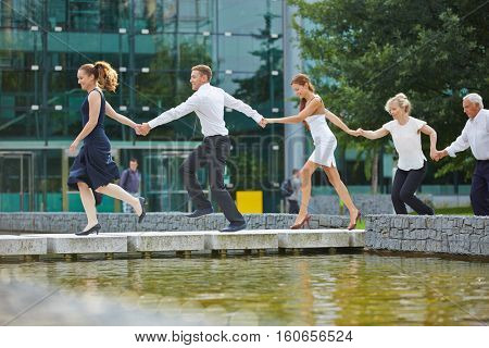 Business team running as a chain in a row with holding hands
