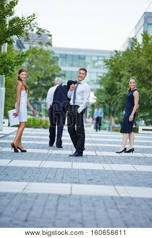 Smiling business people walking in the city to their office