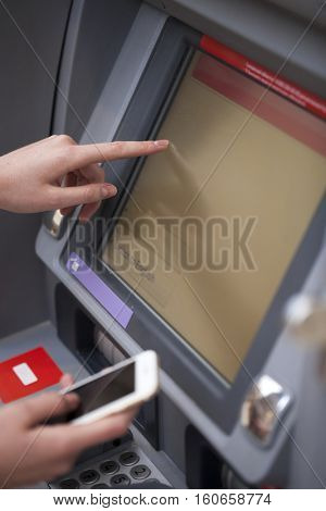 Close up Female hands on the ATM display