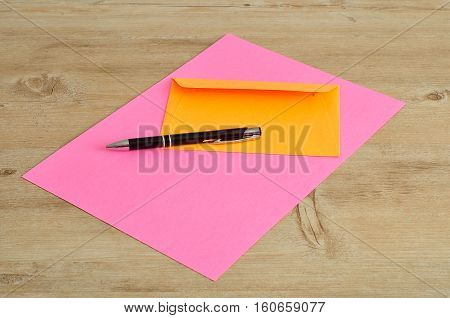 A pink paper and an orange envelope with a black pen