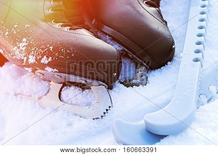 Black Figure Skates Lying In The Snow And Bright Sun