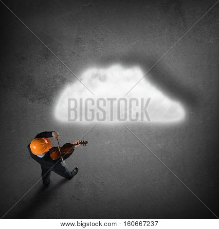 Top view of engineer man playing violin and cloud concept on floor