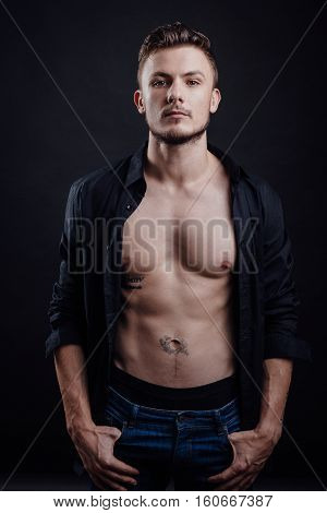 Portrait of handsome guy in naked body with shirt that looking forward on dark background