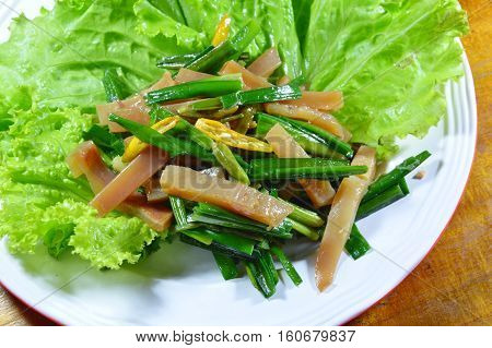 stir fried pickled crispy squid with garlic chives and lettuce on plate